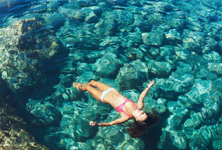 girl floating on back in blue water